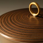 Spun Container with a copper base and Mokume Gane lid made from 5 layers of copper and gilding metal with a gilded metal interior and 9ct gold handle. Ht 10.7cm, Dia 10cm